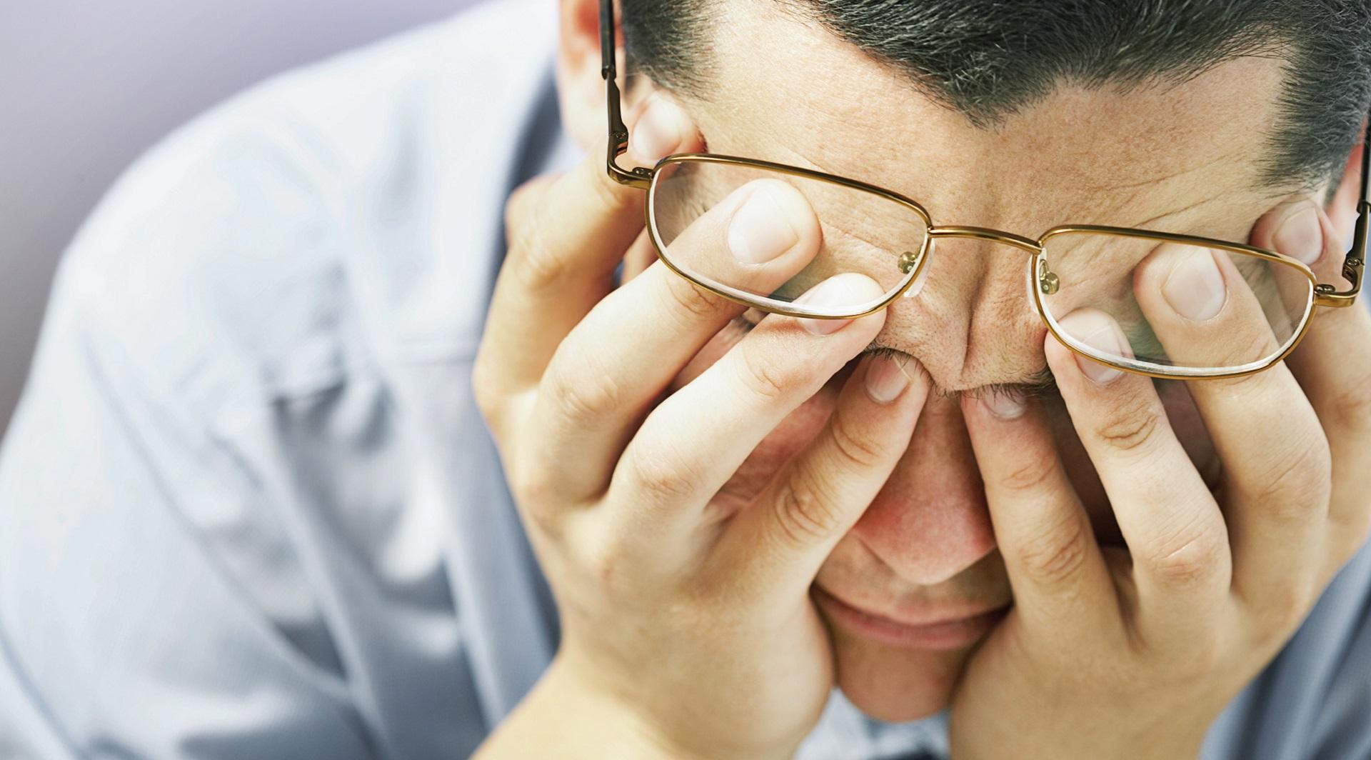Frustrierter, müder Mann im Büro stützt seinen Kopf in den Händen und drückt die Augen zu