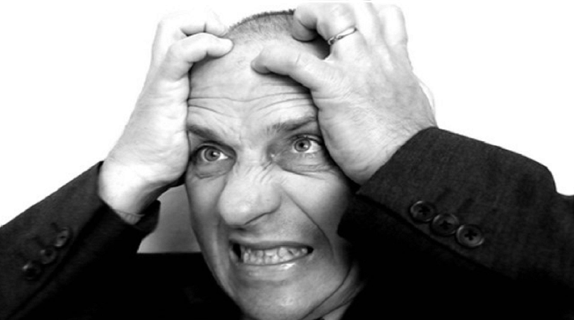 Frustrierter Glatzkopf beißt die Zähne zusammen und gräbt seine Finger in seine Kopfhaut