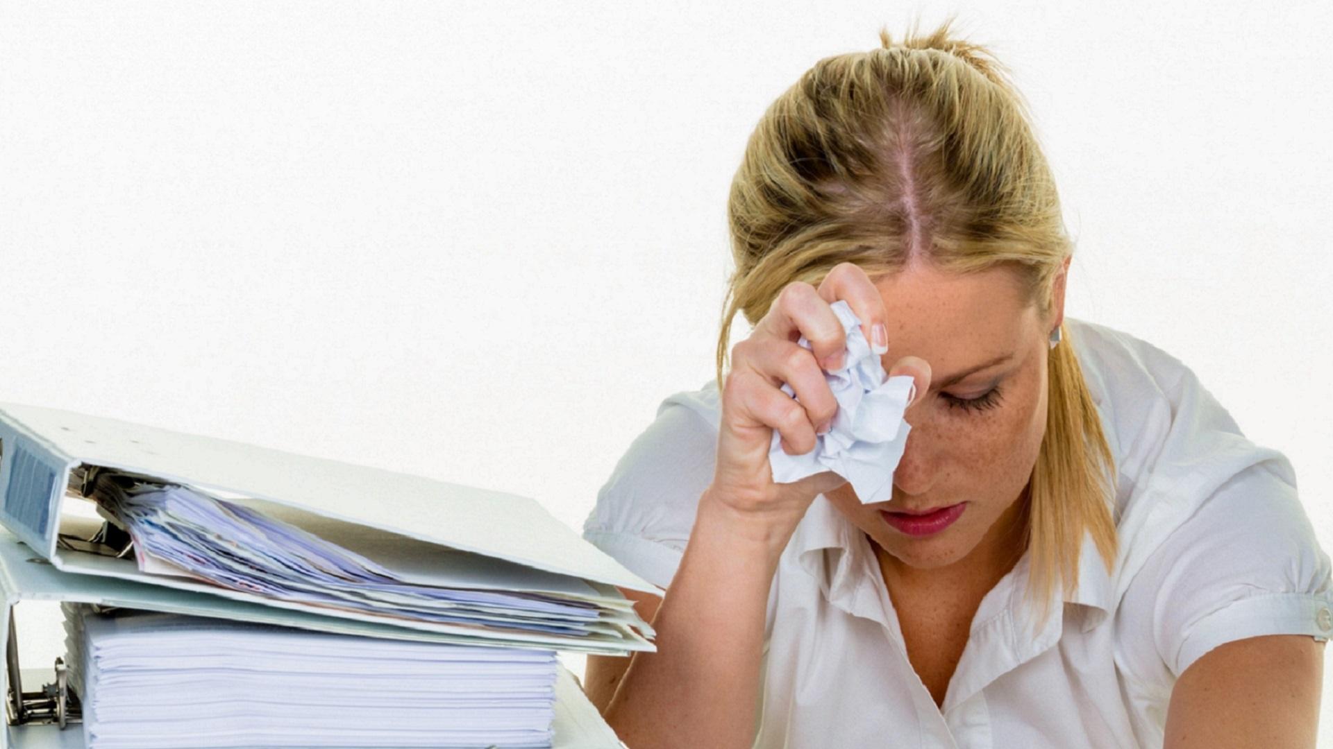 Gestresste, überforderte, weinende junge Frau bei der Arbeit