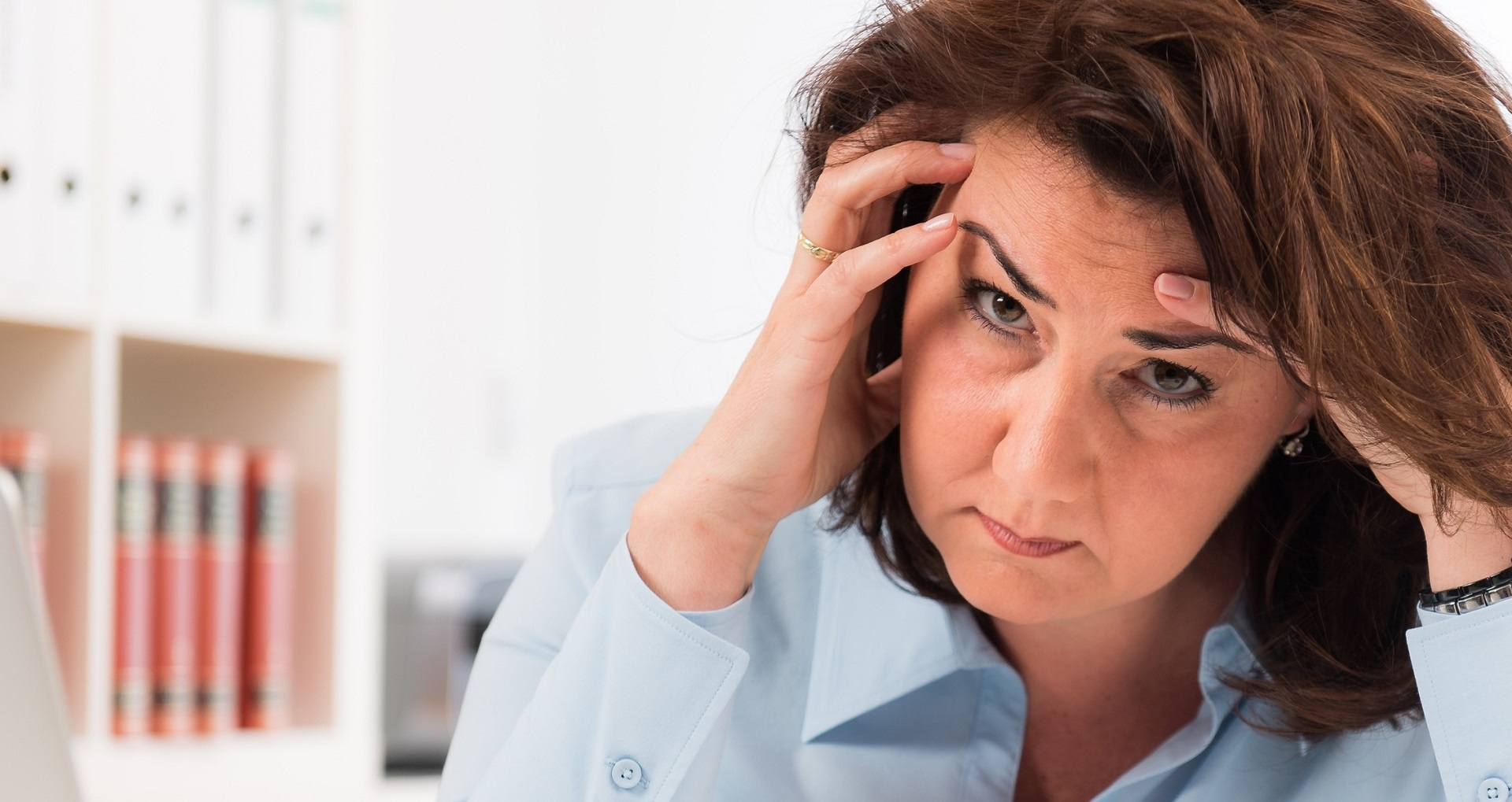 Gestresste, frustrierte Frau am Arbeitsplatz vor einer Bücherwand. Sie hält den Kopf in den Händen.